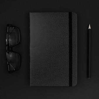 Vista superior da agenda preta e óculos