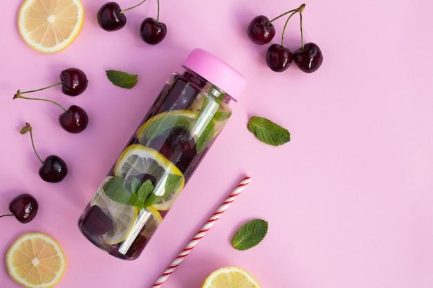 Vista superior da água com infusão de cerejas e limão na garrafa na superfície rosa