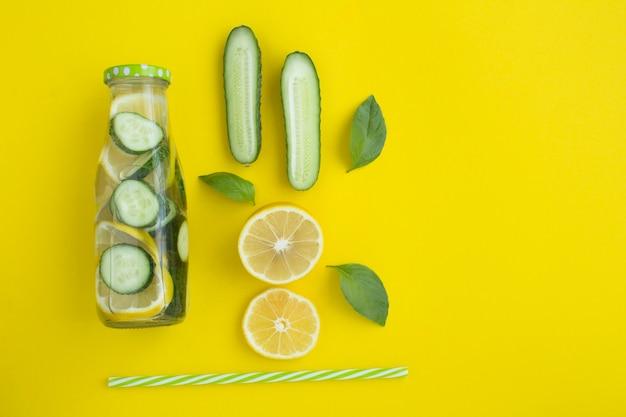 Vista superior da água de desintoxicação com pepino e limão no amarelo