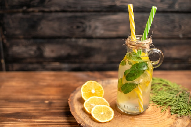Vista superior da água desintoxicante fresca em um copo servido com tubos e limas de limão no lado esquerdo em uma bandeja marrom