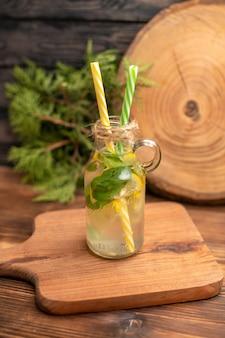 Vista superior da água desintoxicante fresca em um copo servido com tubos em uma tábua de madeira sobre uma mesa marrom