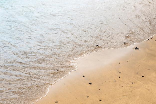 Vista superior da água do mar, tocando a areia na costa