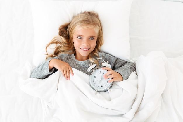 Vista superior da alegre menina loira deitada na cama com o despertador