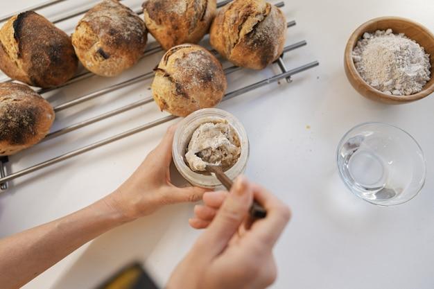 Vista superior da alimentação de farinha fresca para fermento de fermento inicial, misturando-o com uma colher de pau no balcão da cozinha, próximo a pãezinhos recém-assados.