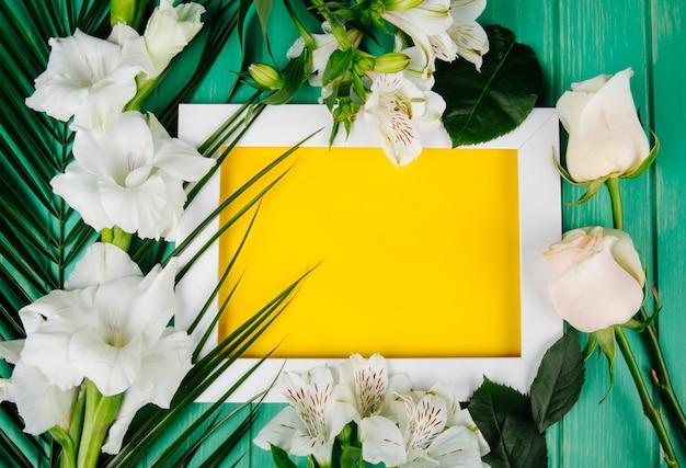 Vista superior da alstroemeria de cor branca e gladíolo com folha de palmeira dispostas em torno de um quadro com folha de papel amarela sobre fundo verde