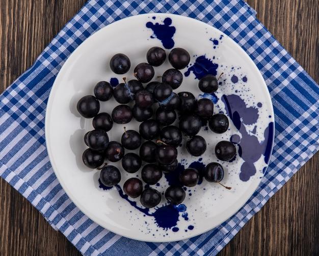Vista superior da ameixa de cereja em um prato branco sobre uma toalha xadrez azul