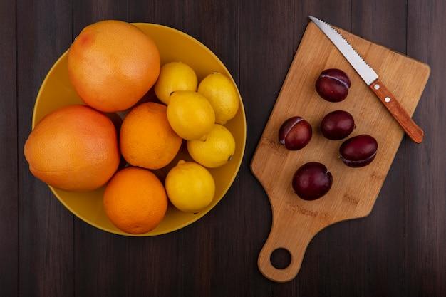 Vista superior da ameixa em uma placa de corte com uma faca com limão, laranja e toranja em uma tigela sobre um fundo de madeira