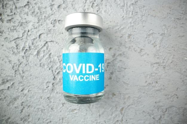 Vista superior da ampola com vacina covid em fundo de areia cinza com espaço livre