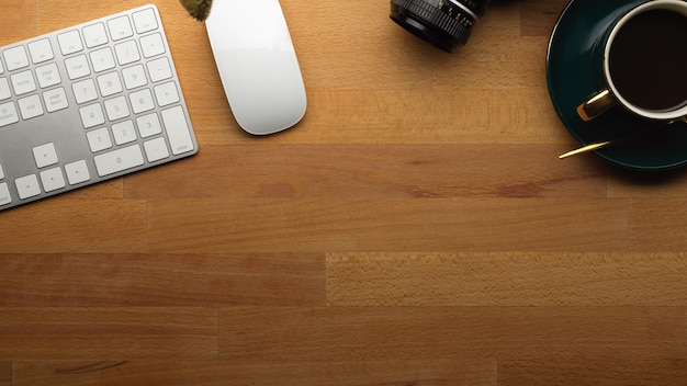 Vista superior da área de trabalho com a xícara de café do mouse do teclado do computador e copie o espaço na mesa de madeira