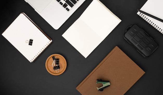 Vista superior da área de trabalho com agenda e laptop