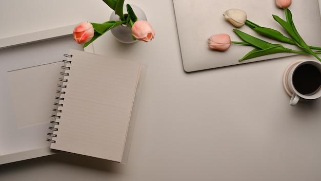 Vista superior da área de trabalho com caderno em branco, moldura, espaço de cópia e flores decoradas na mesa