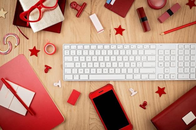 Vista superior da área de trabalho com escritório vermelho estacionário, telefone inteligente e teclado. lat lay. espaço de escritório, conceito de home office