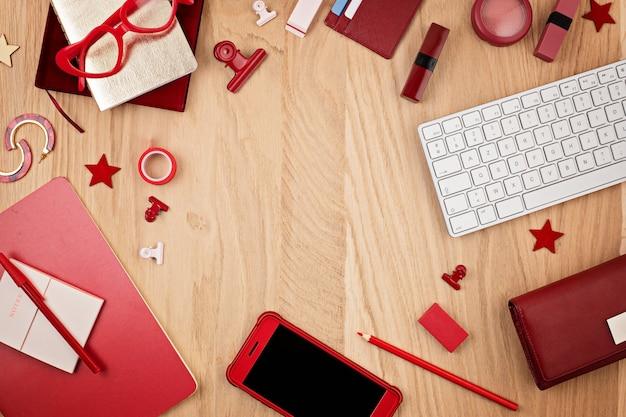 Vista superior da área de trabalho com escritório vermelho estacionário, telefone inteligente e teclado. postura plana. espaço de escritório, conceito de home office