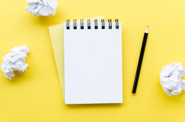 Vista superior da área de trabalho com notebook e papel amassado