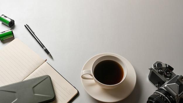 Vista superior da área de trabalho com papel timbrado da câmera da xícara de café e espaço de cópia na mesa branca