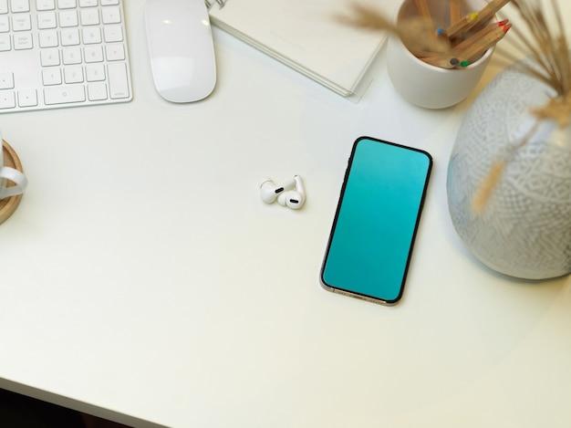 Vista superior da área de trabalho com smartphone, papelaria, fone de ouvido e suprimentos na mesa, área de trabalho criativa plana