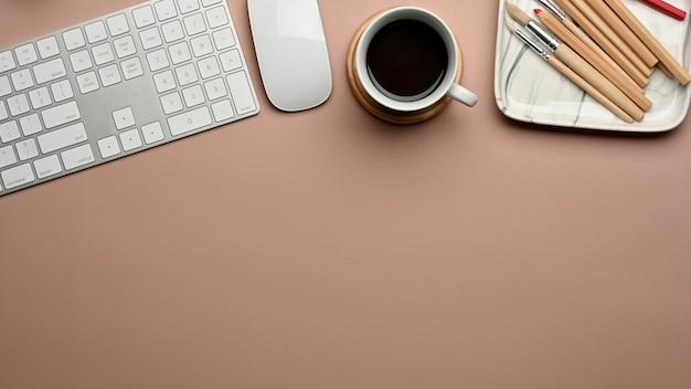 Vista superior da área de trabalho com teclado de computador, xícara de café, suprimentos e espaço de cópia na mesa rosa