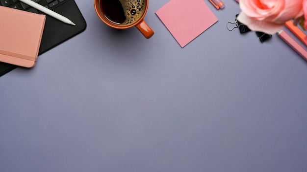 Vista superior da área de trabalho com teclado do tablet, artigos de papelaria, xícara de café, flores e espaço de cópia na mesa roxa