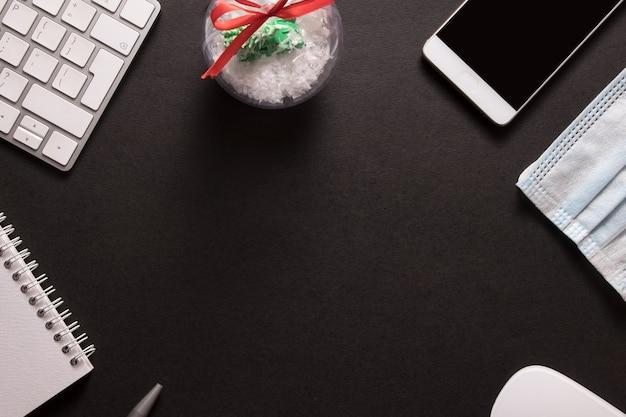 Vista superior da área de trabalho com teclado, mouse, notebook e smartphone com brinquedo de natal com espaço de cópia