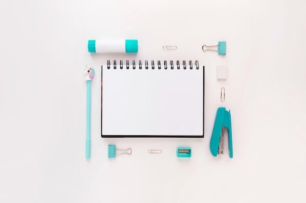 Vista superior da área de trabalho do escritório moderno azul branco com material escolar e artigos de papelaria na mesa ao redor do espaço vazio para texto. de volta ao conceito de escola plana layup com maquete