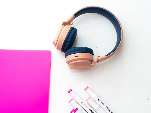 Vista superior da área de trabalho. marcadores profissionais multicoloridos, pasta rosa, fones de ouvido