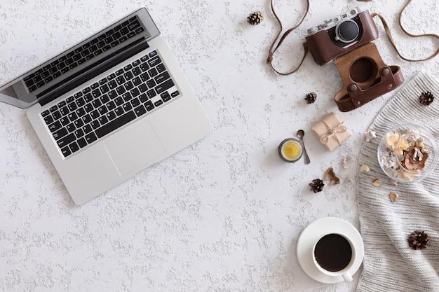 Vista superior da área de trabalho ou mesa de escritório com laptop, câmera fotográfica vintage, cobertor, xícara de café, biscoitos de gengibre