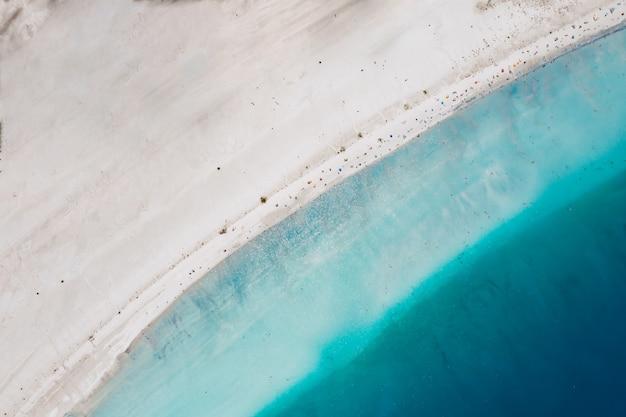 Vista superior da areia encontrando a água do mar