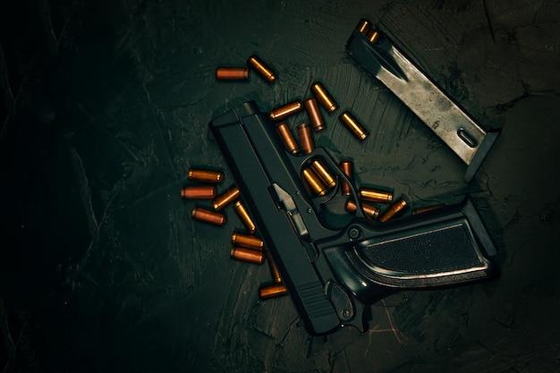 Vista superior da arma e balas planas de pistolas e munições em arma de mesa de concreto escuro ...