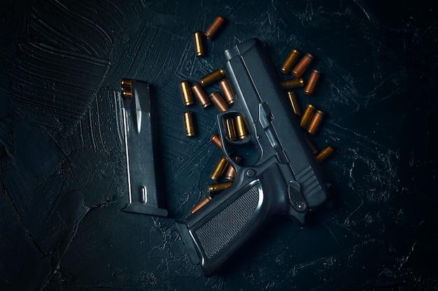 Vista superior da arma e cartucho com armas de balas em pistola de mesa de concreto para defesa ou ataque co ...