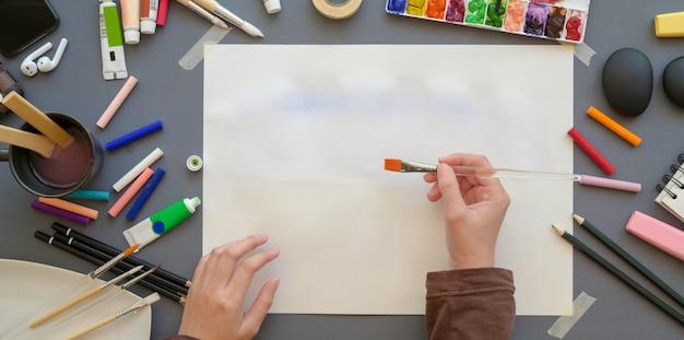 Vista superior da artista feminina pintura em seu projeto com as cores da água, ferramentas de pintura e pincel