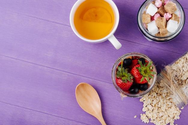 Vista superior da aveia durante a noite com iogurte de mirtilos morangos frescos e nozes em uma jarra de vidro com uma xícara de chá verde na superfície de madeira roxa com espaço de cópia