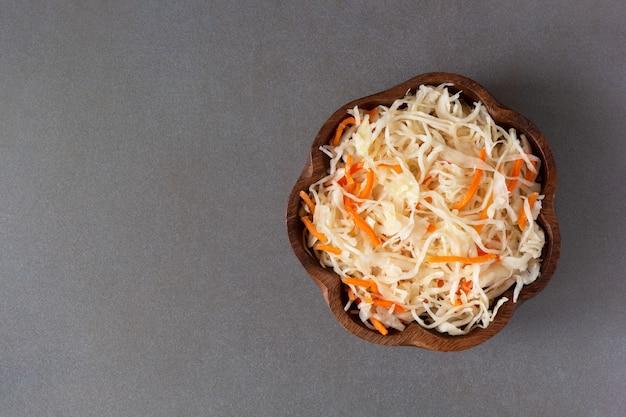 Vista superior da bacia de madeira do sauerkraut e da cenoura no fundo neutro.