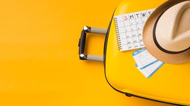 Vista superior da bagagem com chapéu e calendário e cópia de espaço