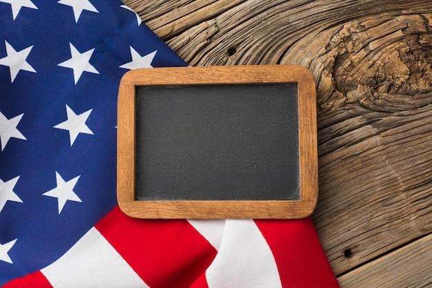 Vista superior da bandeira americana e quadro-negro na madeira