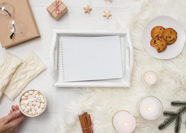 Vista superior da bandeja com caderno e biscoitos