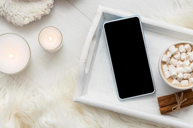 Vista superior da bandeja com smartphone e xícara de chocolate quente com marshmallows