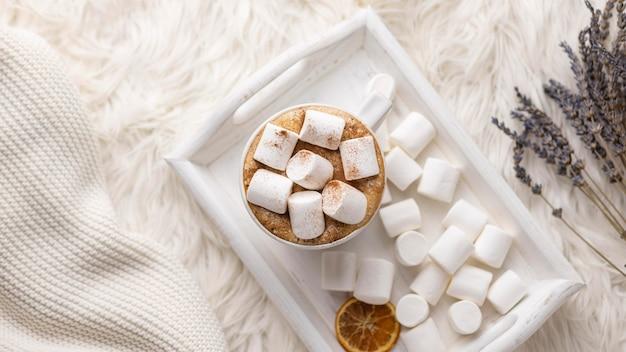 Vista superior da bandeja com xícara e marshmallows com lavanda