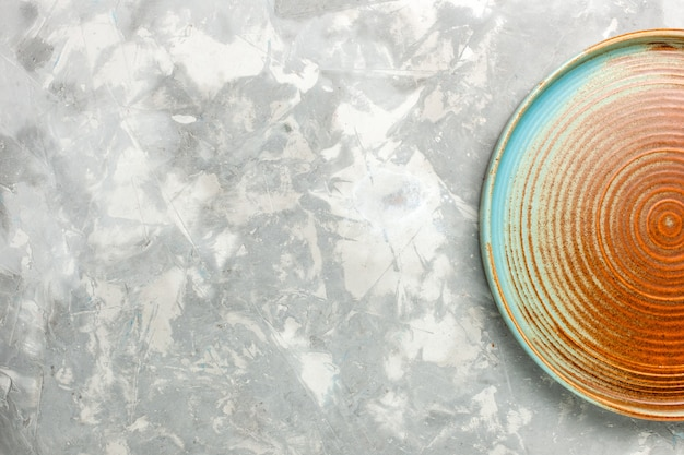 Vista superior da bandeja redonda marrom vazia isolada na superfície cinza