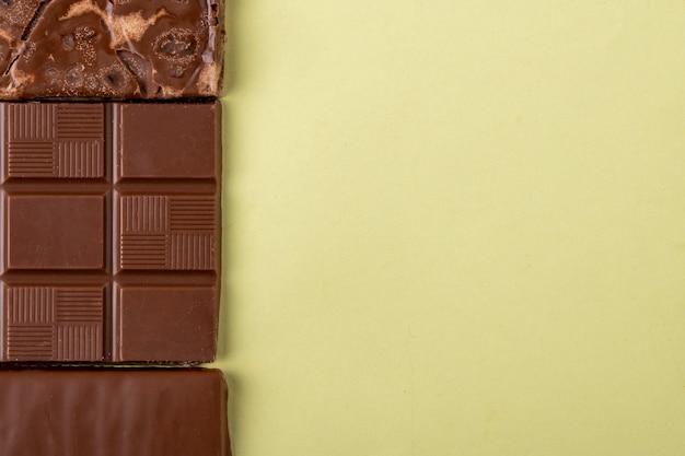 Vista superior da barra de chocolate na luz colorida de fundo com espaço de cópia
