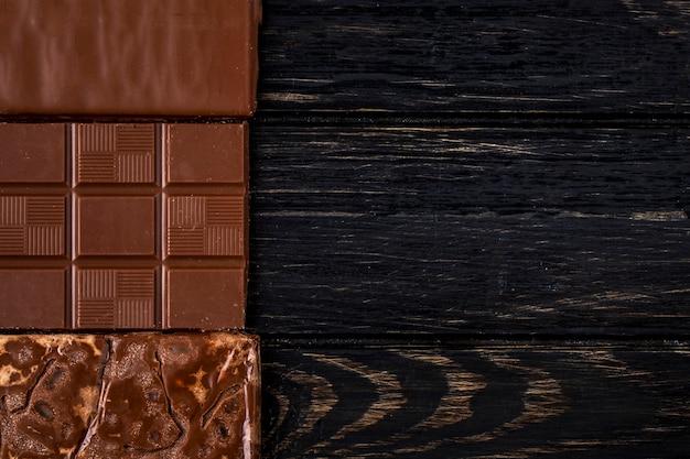 Vista superior da barra de chocolate no fundo rústico escuro, com espaço de cópia