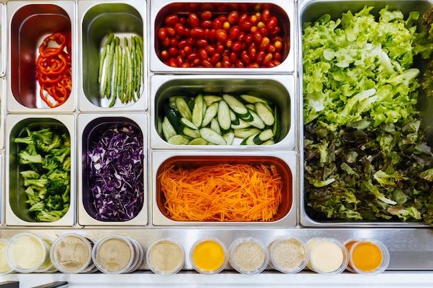Vista superior da barra de salada com a variedade dos ingredientes para a refeição saudável e da dieta.