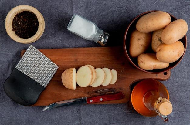 Vista superior da batata fatiada e faca com cortador de microplaqueta de batata na placa de corte com outros na manteiga de sal pimenta tigela preta na superfície do pano cinza