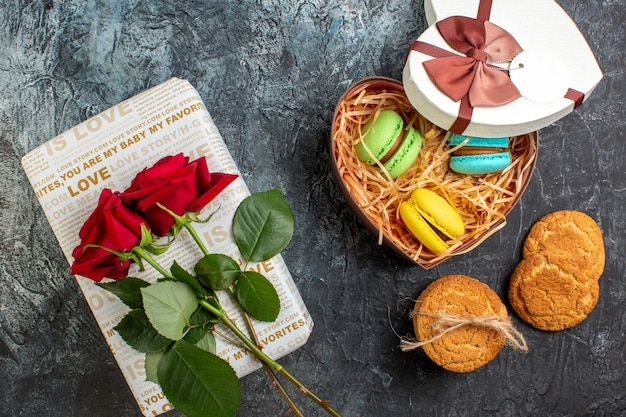 Vista superior da bela caixa de presente em forma de coração com deliciosos macarons e biscoitos de rosa vermelha em fundo escuro glacial