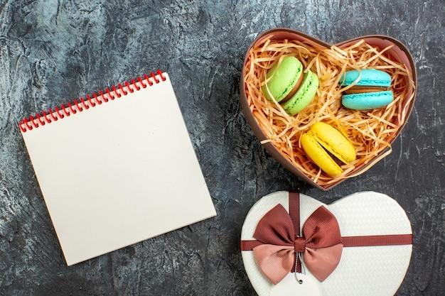 Vista superior da bela caixa de presente em forma de coração com deliciosos macarons e caderno espiral em fundo escuro glacial