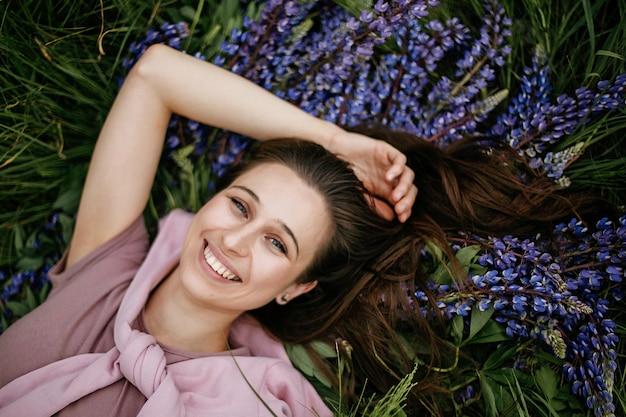 Vista superior da bela jovem morena deitada na grama verde e tremoços violetas selvagens