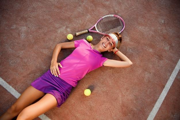 Vista superior da bela jovem sorridente em uniforme rosa e boné desportivo situa-se na quadra de tênis ao ar livre com muitas bolas após um treinamento bem-sucedido ao pôr do sol.