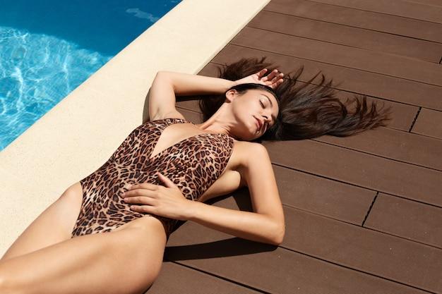 Vista superior da bela mulher sexy, deitado perto da piscina, vestindo calção de leopardo, relaxante com os olhos fechados, com longos cabelos negros, banhos de sol com prazer. conceito de atividades de lazer.