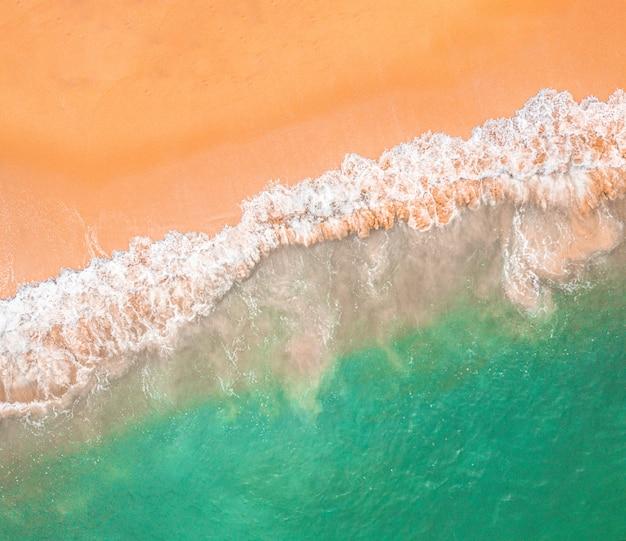 Vista superior da bela praia de areia com água azul-turquesa do mar