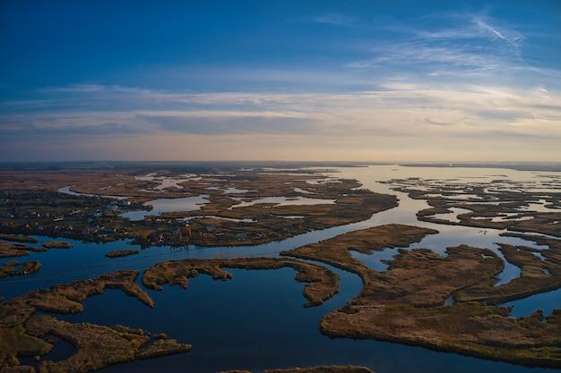 Vista superior da bela samarskie plavni no dnieper com uma vila próxima à luz quente da noite