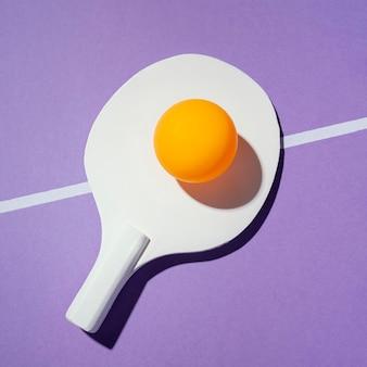 Vista superior da bola amarela na raquete de pingue-pongue